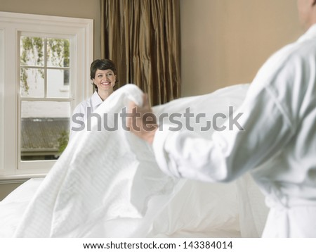 Happy woman making bed with man