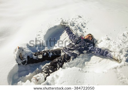 Happy woman making snow angel in the snow. Ski. Funny female skier on the background of high snow-capped Alps in Swiss - stock photo
