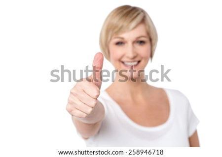 Happy woman making thumbs up gesture - stock photo