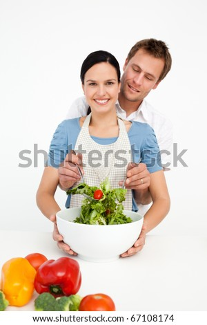 Happy woman mixing a salad with her boyfriend in the kitchen at home - stock photo