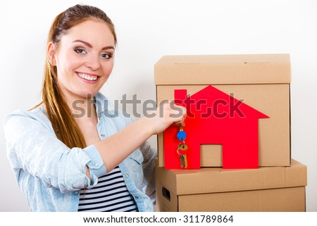 Happy woman moving in carrying cartons boxes with red paper house and key. Young girl arranging interior and unpacking at new apartment home.
