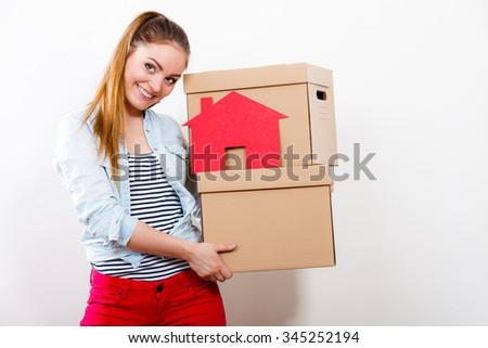 Happy woman moving into new apartment carrying cartons boxes with red paper house. Young girl arranging interior and unpacking at home.