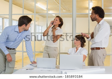 Happy woman on call amid business meeting at the office - stock photo