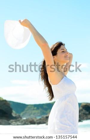 Happy woman on nature beach on summer vacation. Beautiful caucasian girl raising arm and holding white hat. Playa de Verdicio, Asturias, Spain. - stock photo