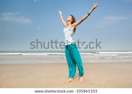 Happy woman on the beach arms stretched