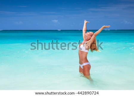 Happy woman on the beach with raised up hands, enjoying bright sunny day, travel to islands