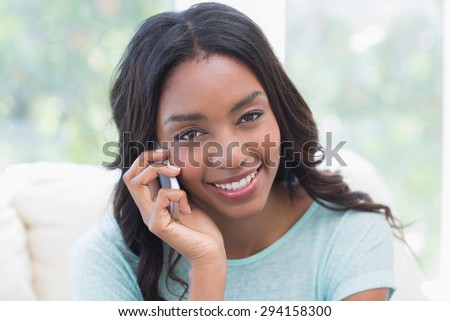 Happy woman on the phone at home in the living room - stock photo