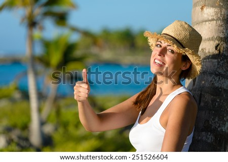 Happy woman on tropical vacation doing success thumb up gesture and smiling. Brunette girl enjoying caribbean travel. - stock photo