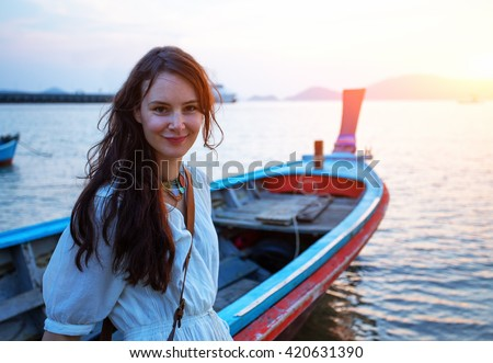 Happy woman on vacation in Thailand. Pretty young girl standing on the sunset beach in front of  traditional longtail fishing boat. Holiday trip on Phuket. - stock photo