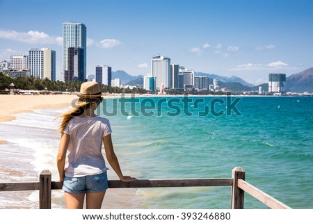 Happy woman on wooden pier enjoying sea view, big city on the background