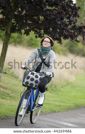 Happy woman outdoors on blue bicycle - stock photo