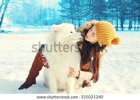 Happy woman owner and white Samoyed dog in winter day - stock photo
