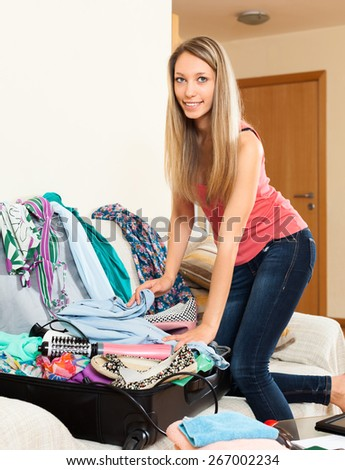Happy woman packing clothes and accessories into suitcase - stock photo