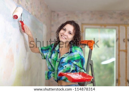 Happy woman paints wall with roller at home - stock photo