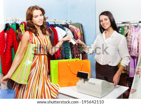 Happy woman paying with credit card for purchase - stock photo