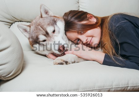 Happy woman petting her siberian husky at home