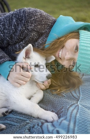 Happy woman petting her white cuddling dog puppy