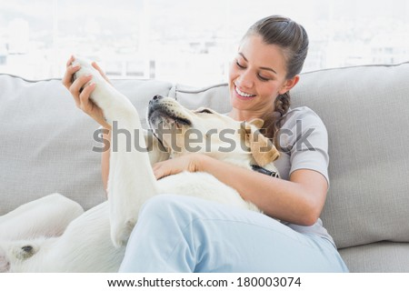 Happy woman petting her yellow labrador on the couch at home in the living room - stock photo