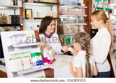 Happy woman pharmacist standing with a cash desk in the pharmacy and helping customers