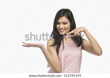 Happy woman pointing at her hand
