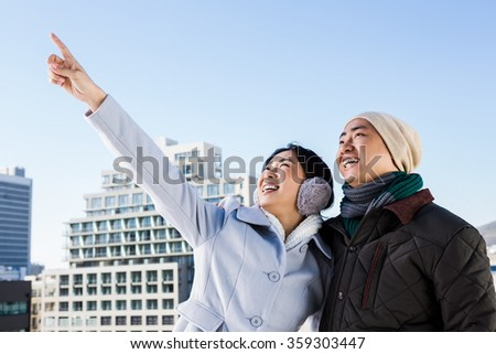 Happy woman pointing finger with boyfriend against sky