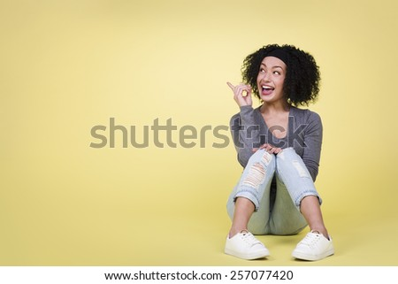 Happy woman pointing up at empty copy space being excited, isolated on yellow background. - stock photo