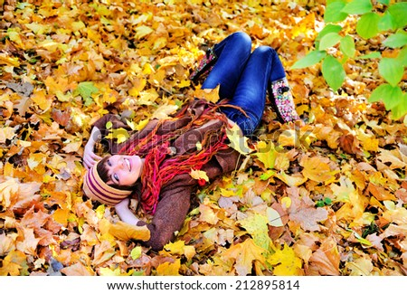 Happy woman portrait lying on autumn leaves in park and looking at camera.  - stock photo