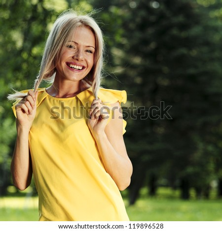 happy woman posing against a background of trees - stock photo