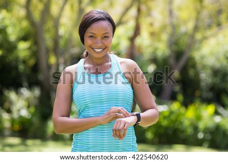 Happy woman posing and touching her watch - stock photo