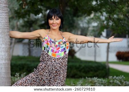 Happy woman posing by a tree in the garden - stock photo