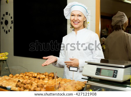 Happy woman posing in bakery with baguettes and buns - stock photo