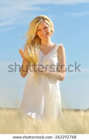 Happy woman posing in white dress in golden wheat. - stock photo
