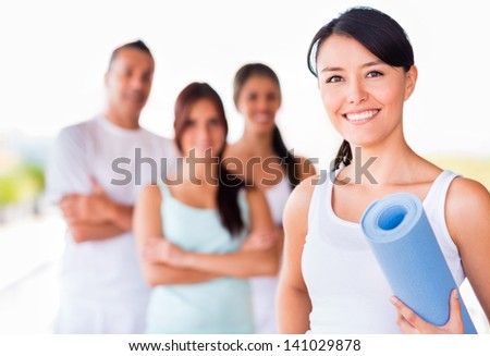 Happy woman practicing yoga and holding a mat - stock photo