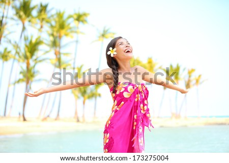 Happy woman praising freedom smiling on hawaiian palm beach in sarong, arms stretched out. Beautiful mixed race female model enjoying sun in worship and meditation zen. Big Island, Hawaii, USA. - stock photo