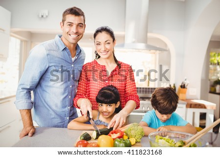 Happy woman preparing food with family by table at home - stock photo