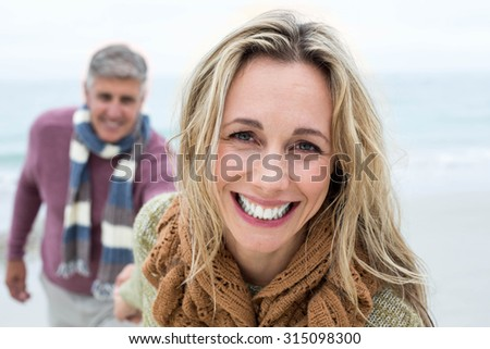 Happy woman pulling her partner towards her at the beach - stock photo