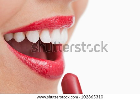 Happy woman putting lipstick on her lips against a white background - stock photo