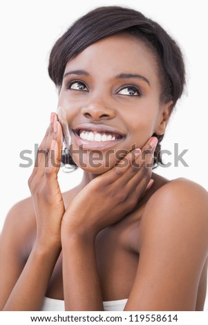 Happy woman putting on face cream on white background - stock photo