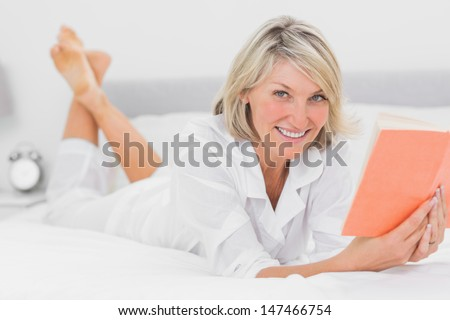 Happy woman reading a book lying on bed at home in bedroom - stock photo