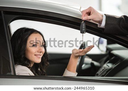 Happy woman receives the keys to a new car from a sales manager. - stock photo