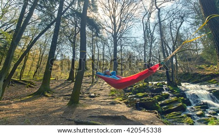 Happy woman relaxes, lying in a hammock in forest, adventure outdoor activity                                 - stock photo