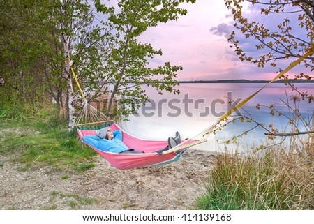 Happy woman relaxes, lying in a hammock in sunny spring day. enjoy sunset at hammock