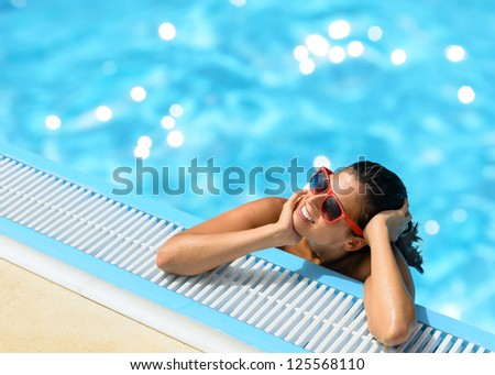 Happy woman relaxing and enjoying summer at pool. Beautiful brunette caucasian girl with red sunglasses on summer vacation into swimming pool. Copy space. - stock photo