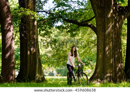 Happy woman relaxing and walking trough the park with a bicycle,