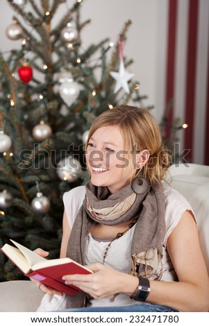 Happy woman relaxing at Christmas with a book as she sits on a sofa in front of the tree laughing happily at someone off frame - stock photo