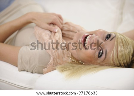 Happy woman relaxing at home laughing on sofa