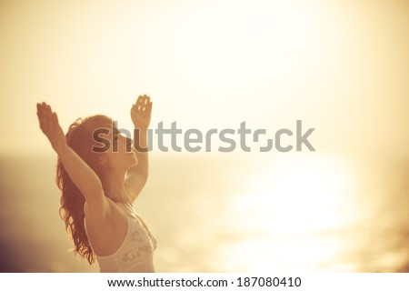 Happy woman relaxing at the beach. Summer vacation and freedom concept. Instagram style toned photo - stock photo