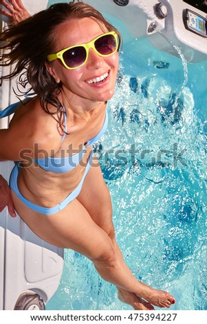 Happy woman relaxing in hot tub.