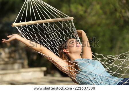 Happy woman relaxing on a hammock on holidays and raising arms in the mountain - stock photo
