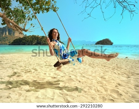Happy woman relaxing with hanging swing on tropical beach - stock photo